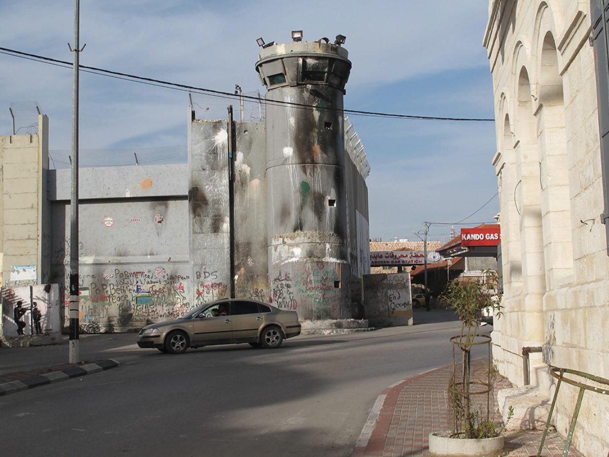 A sooty watchtower, part of the wall separating Bethlehem from Jerusalem, looms over Hebron Road in the West Bank. Photo Byron Rempel-Burkholder