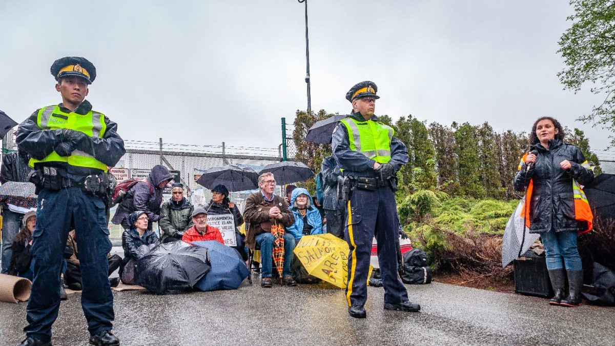 Song leader, police and gate blockers in front of the Kinder Morgan gates. Photo by Kimiko Karpoff