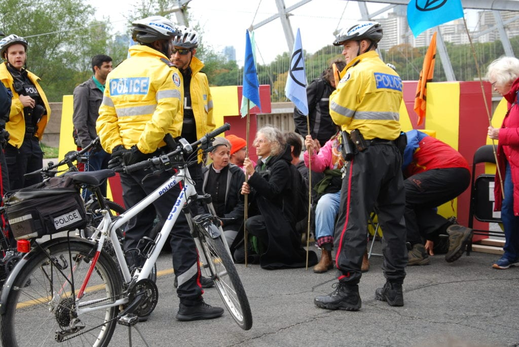 Protesters sit and face police during the demonstration. (Photo: Aleysha Haniff)