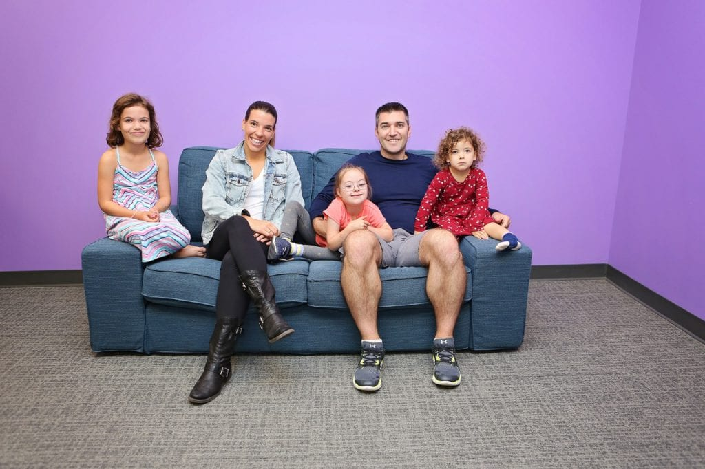 Family, including three daughters, one with Down syndrome, poses on couch
