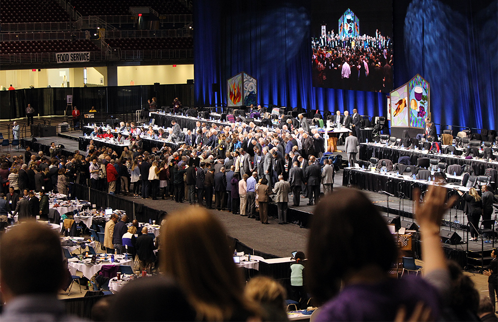 United Methodist bishops and delegates gather together to pray at the front of the stage before a key vote on church policies about homosexuality on Feb. 26, 2019, during the special session of the General Conference of The United Methodist Church, held in St. Louis, Mo. (Photo: Kit Doyle/RNS)