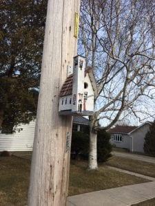 A white birdhouse shaped like a church is seen on a telephone pole.